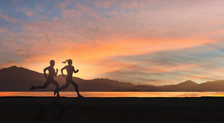 Young couple run together at sunset