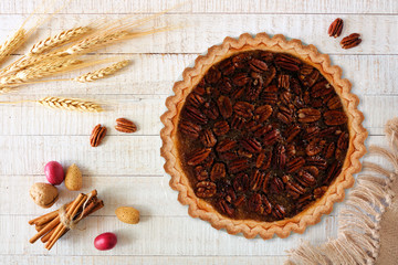Homemade pecan pie, above view table scene with a white wood background
