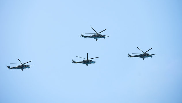 Military helicopters maneuvers in the blue sky. Group combat helicopters in flight during a military demonstration