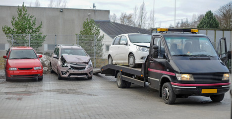 Broken car on tow truck after traffic accident