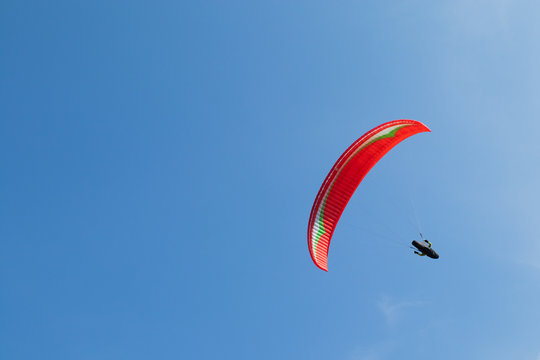 Red paraglider isolated on a clear blue sky