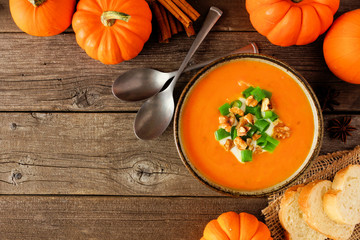 Creamy pumpkin soup. Autumn food concept. Top view scene on a rustic wood background with copy space.