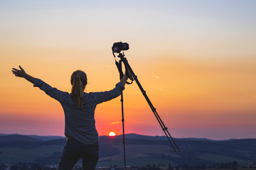 Enjoying spending time with camera in nature. Photographer holding a tripod and looking at sunset.