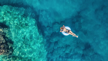 Aerial view at the girl on sea. Turquoise water from air as a background from air. Natural seascape at the summer time. Seascape from drone