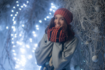 A cheerful and sweet girl in a hat and a warm sweater for Christmas or New Year's Eve