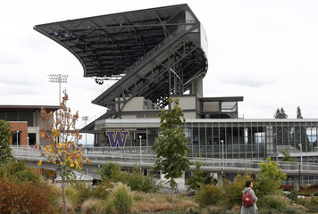 A woman walks by Alaksa Airlines Field and University of Washington light rail station in Seattle Washington