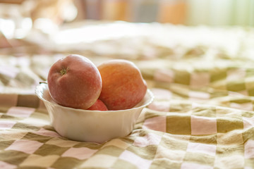 close up hands holding a plate with fresh raw fruit apples in bed in the morning f
