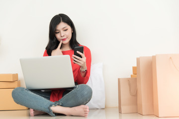 Asian women buying goods online through computer and cell phone.