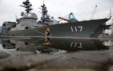 Locals look at Japanese destroyers Inazuma and Suzutsuki anchored at a port in Jakarta
