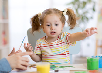 Cute child toddler girl in striped shirt and pony tails paints in the art class