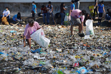 Volunteers pick up trash along Manila Bay for World Coastal Clean Up Day, in Manila