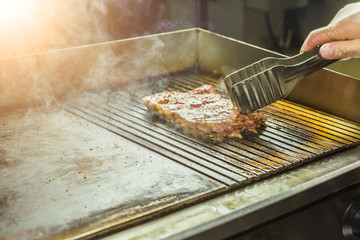 Food and cooking concept - Close up of a steak on grill