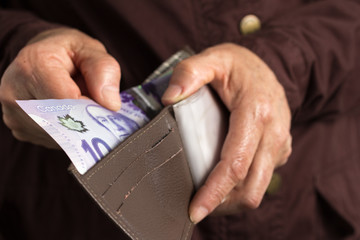 Canadian currency. Dollars. Old retired person paying in cash.