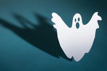 Halloween background concept. Funny ghost doing boo gesture and graphic shade behind on blue table.