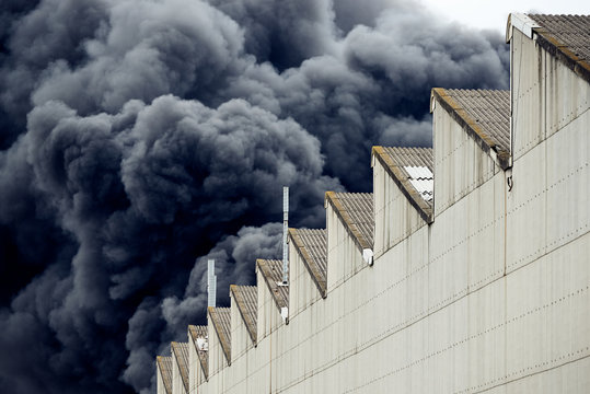 Black plumes of smoke from an accidental toxic industrial fire as seen from a behind a factory building.