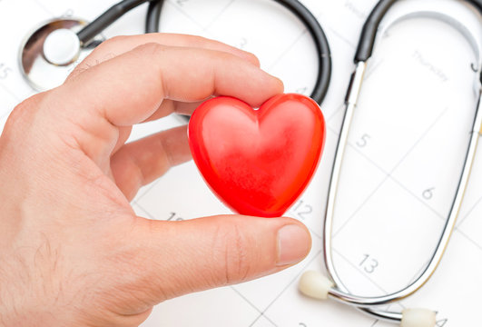 Man's hand holding red heart over calendar and stethoscope.