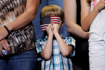 A young boy holds the American flag in front of his face as U.S. President Donald Trump arrives at a campaign rally in Springfield