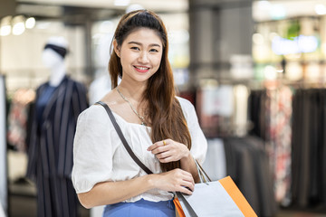 Beautiful Attractive Happy Asian Woman smile and enjoy with shopping bags in shopping mall,Shopping Concept