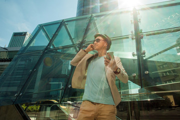 Man listening to music on phone and dancing against the background of skyscrapers. Travel and lifestyle concept.