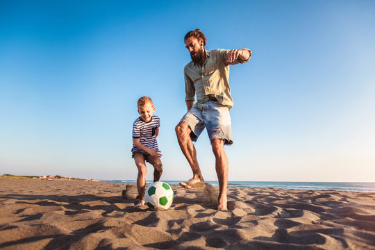 Happy father and son play soccer or football on the beach having great family time on summer holidays.