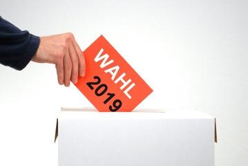 Hand mit Wahlurne und Stimmzettel: Wahl 2019