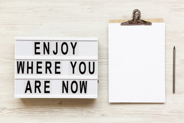 'Enjoy where you are now' words on lightbox, noticeboard, pencil over white wooden background, overhead. Top view, flat lay, from above.