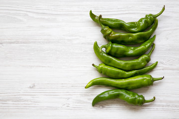 Green chili peppers on white wooden background, top view. Flat lay, from above, overhead. Copy space.