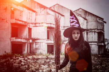 Halloween young woman in witches hat stands and a broom in hand on a black building background.