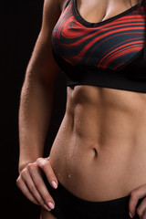 Caucasian fitness instructor female in active wear, demonstrates her perfect body shape. Cropped studio shot of a stunning hot sporty body of a fitness woman
