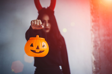Young woman in black dress with red devil and orange pumpkin in hand is on a black background, Halloween concept. Horror theme.