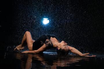 Fashion girl lying in black aqua studio