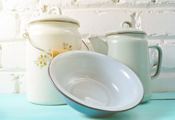 Lot of enameled dishes on a blue table against white brick wall background. Retro style cookware.
