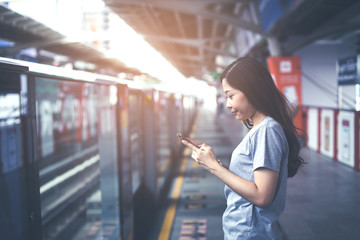 Young woman waiting for electric trains on the platform and using the smart phone to find the route.