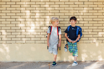 Two boys with backpacks leaning at brickwall