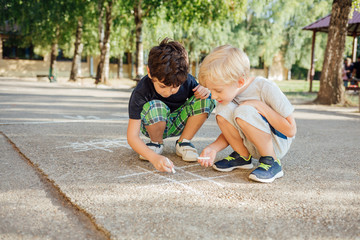 Two boys drawing with chalk