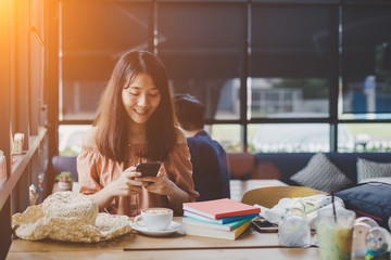 Young woman is playing mobile and a cup of coffee is placed on the table smiling happily, Enjoy eating. Looking mobile phone.