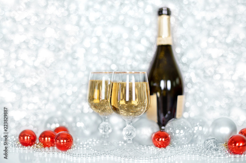 two glasses of champagne and a bottle of champagne new years red and white balls