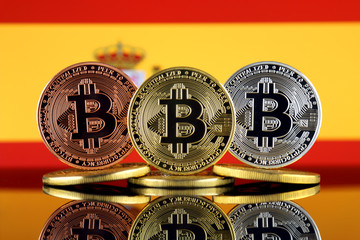 Physical version of Bitcoin (BTC) and Spain Flag. Conceptual image for investors in High Technology (Cryptocurrency, Blockchain Technology, Smart Contracts, ICO).