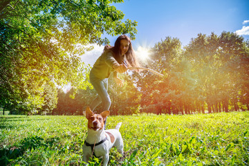 girl teenager walks with her dog jack russel terrier in the park, the girl throws a stick to her pet, the animal is trained