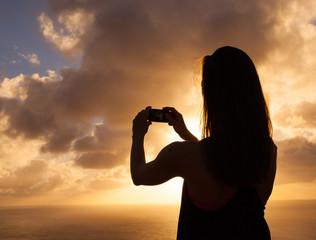 Female taking photo of a beautiful sunset.