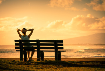 Young woman sitting back relaxing watching the beautiful sunset.