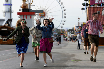 Visitors run to get a spot at the Oktoberfest area at the opening day of the 185th Oktoberfest in Munich