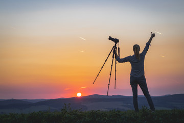 Female photographer holding a tripod with camera and looking at sunset. Woman enjoying spending time with camera in nature.