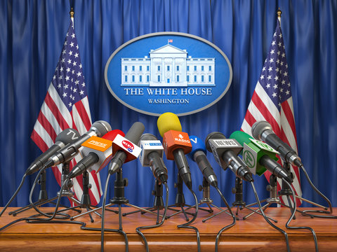 Press conference of president in the White House Washington.  Microphones  of all media with USA flags and White House sign.