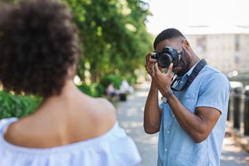 African-american photographer taking photos of beautiful woman