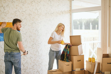 young couple hanging picture on wall together while moving into new home