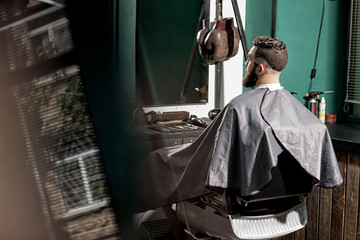 Brutal man with stylish hairstyle and beard sits at a barber shop in front the mirror