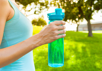 Female holding bottle of water.