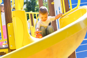 A cute two-year-old boy in a white t shirt sliding down on a yellow slide on a playground