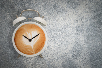 Hot coffee with frothy foam in white alarmclock design is Coffee Time Concept